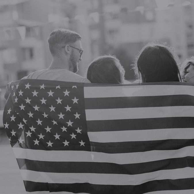 Image of a man and two females with backs turned and drapped with the American Flag