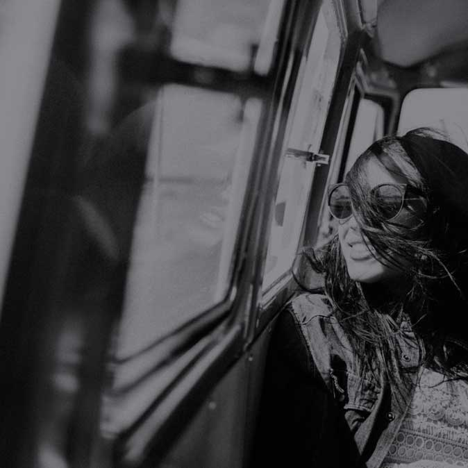 Young smiling female with sunglasses rests in a passenger seat looking out the window with the wind bursting through her hair