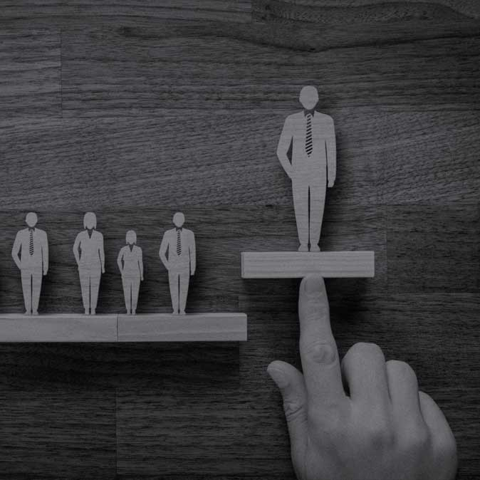 Professional looking men and women wooden figures standing on a shelf, a hand with its index finger pointed is raising a portion of the shelf with male wooden figure on it.