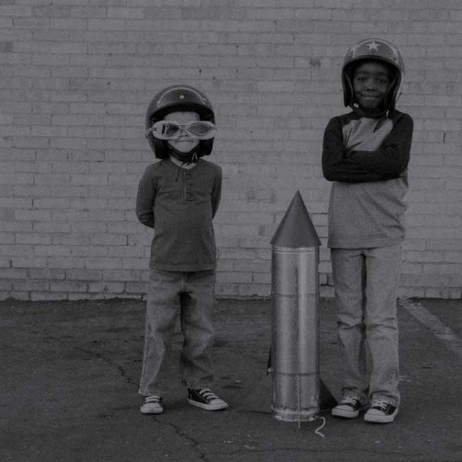 Two young boys standing with a toy rocket between them.